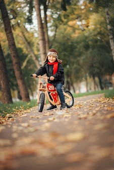 Little boy riding a balance bike in the city in autumn