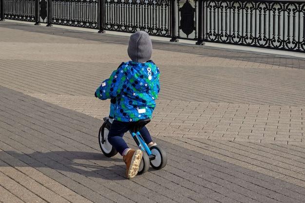 Little boy riding a balance bike on a city sidewalk