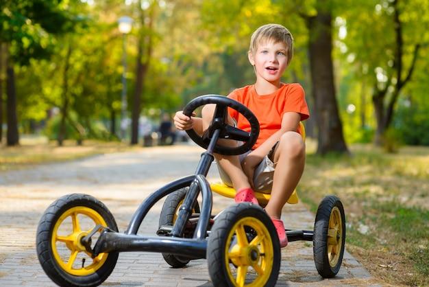 夏の都市公園で小さな男の子乗馬おもちゃの車
