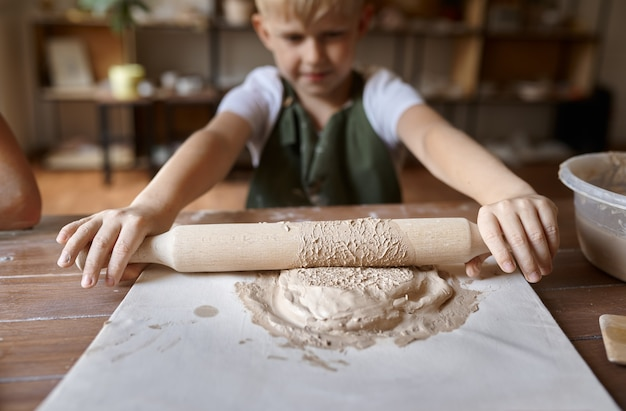 Маленький мальчик раскатывает глину за столом, малыш в мастерской. урок в художественной школе. юный мастер народных промыслов, приятное увлечение, счастливое детство.