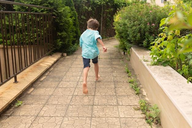 Маленький мальчик работает на заднем дворе бассейна