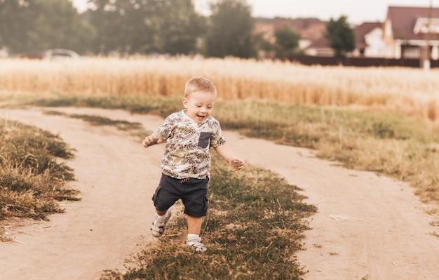 夏に田舎道を走っている少年