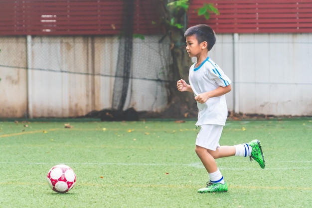 Little boy running with soccer ball in football field