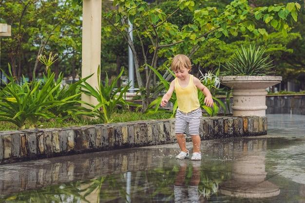 小さな男の子が水たまりを駆け抜ける