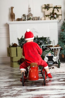 Little boy in santa claus costume rides a toy red car
