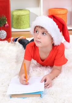 Little boy in santa hat writes letter to santa claus
