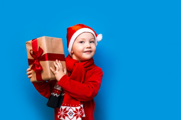 Little boy in santa's hat with cozy gift box and red tape