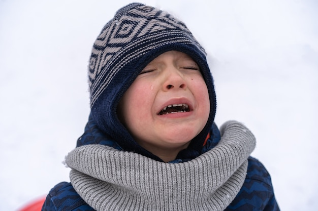 小さな男の子は悲鳴を上げて泣きます。感情。冬服の少年