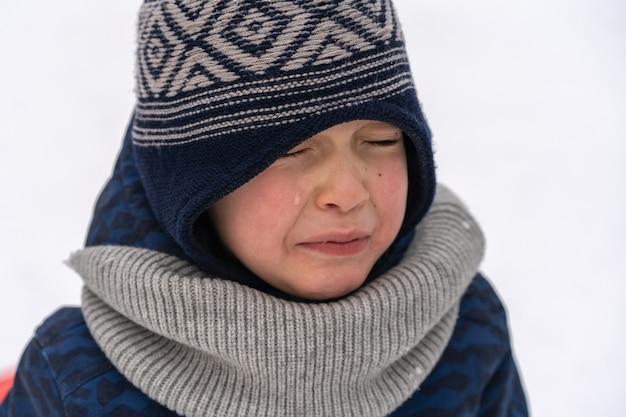 Маленький мальчик кричит и плачет. эмоции. мальчик в зимней одежде