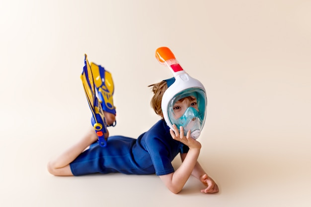 Little boy in scuba mask and snorkel on sand background.