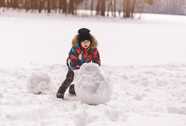 Little boy sculpts a snowball in winter in the park