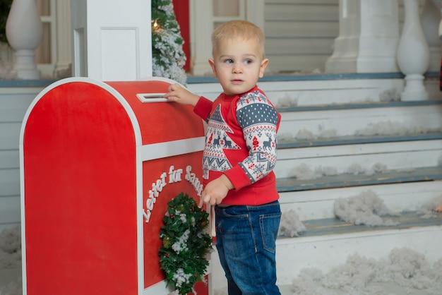 Маленький мальчик отправляет письмо деду морозу