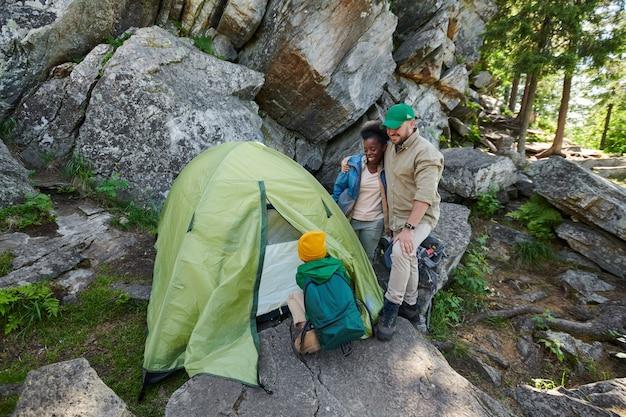 Маленький мальчик устанавливает палатку, пока его родители стоят и наблюдают за ним, они находятся в скалах во время похода