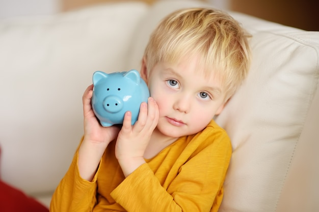 Little boy shaking a piggy moneybox and dreams of what he can buy.