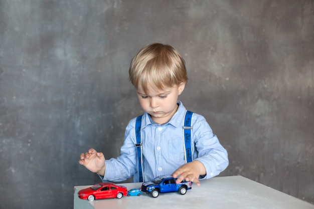 A little boy in a shirt with suspenders plays with toy multi colored toy cars. preschool boy playing with toy car on a table at home or daycare. educational toys for preschool and kindergarten child.