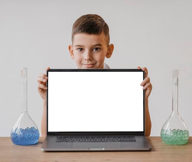 空白の画面のラップトップを見せている小さな男の子