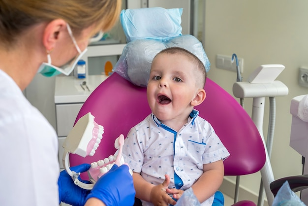 Little boy showing his teeth to a doctor