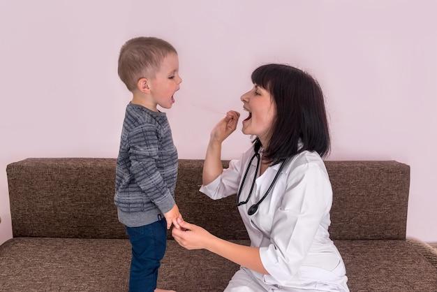 医者に喉を見せている少年