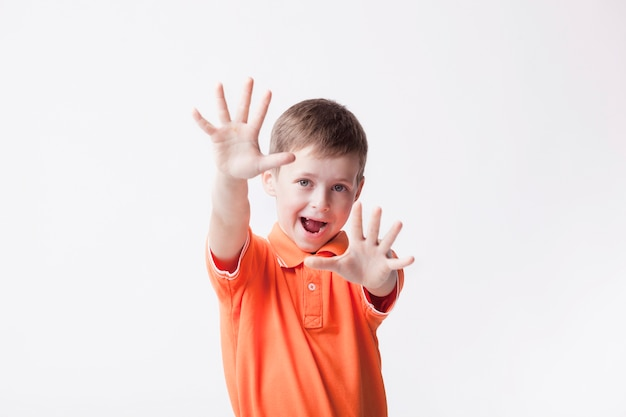 Little boy showing stop gesture with mouth open over white background