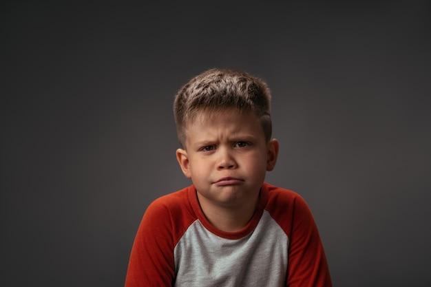 Маленький мальчик показывает своим лицом, что мне это не нравится его родителям, изолированным на сером фоне