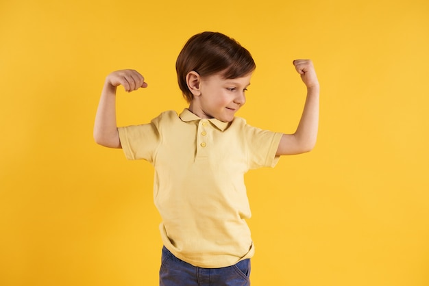 Little boy shows biceps isolated on yellow