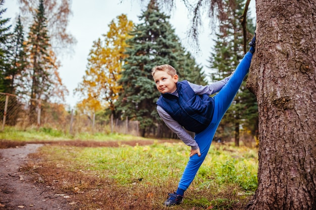 Little boy shows splits standing by the tree in the forest