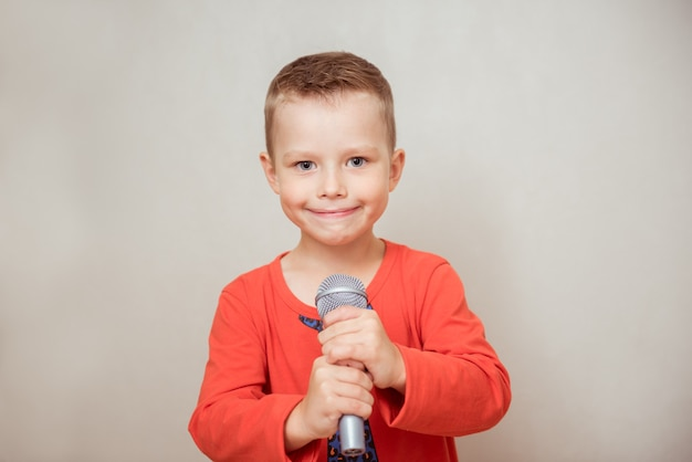 Little boy singing with microphone on gray background. music, song and education concept