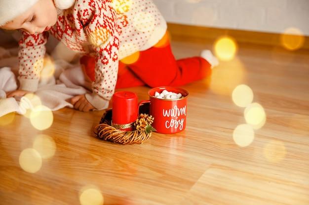 マシュマロのクリスマスとホットチョコレートのカップをすすりながら小さな男の子