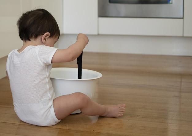 小さな子供は台所の木製の床に座って台所用品で遊ぶ