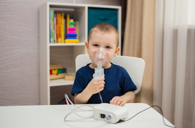 Маленький мальчик сидит за столом в комнате и вдыхает через небулайзер