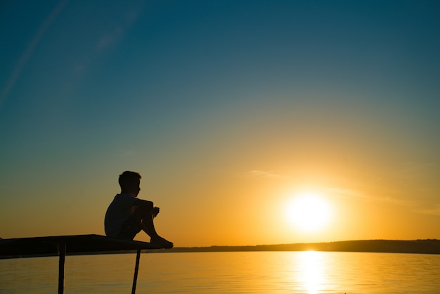 The little boy sits on a bridge and looks at sunset by the river.