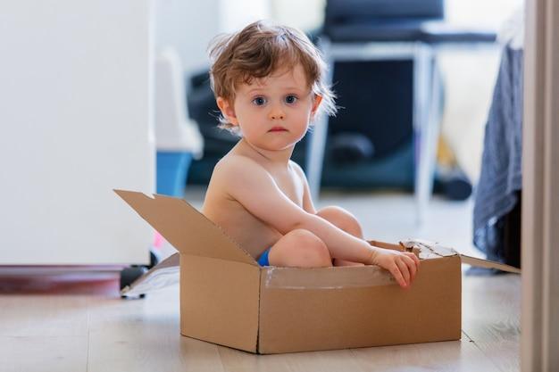 小さな男の子は家の床の箱に座っています