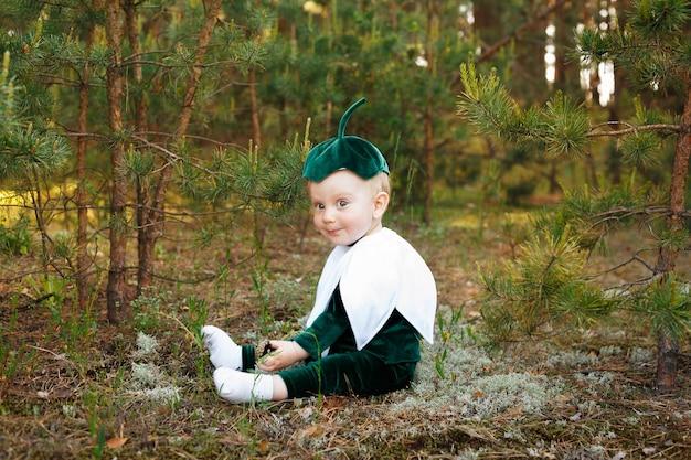Маленький мальчик сидит на лесной тропе в костюме подснежника. мальчики, одетые в забавный костюм подснежника с шляпой
