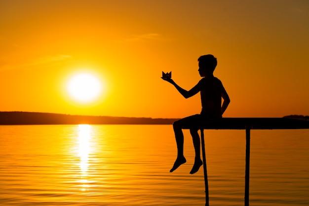 小さな男の子は日没時に橋の上に座っています。