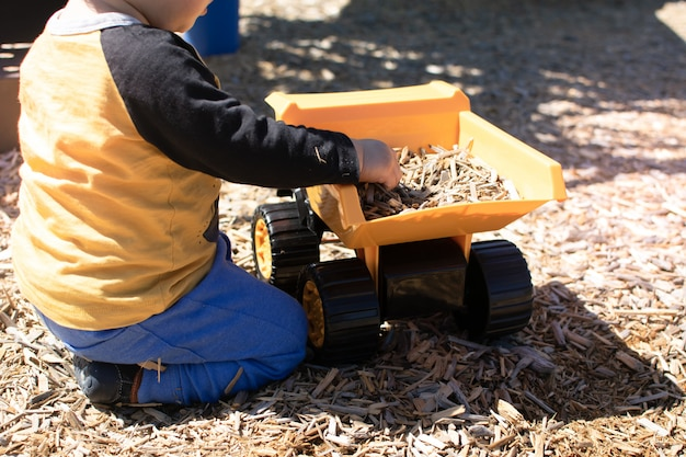 Little boy sits and plays by puts the wood chips to the yellow truck toy