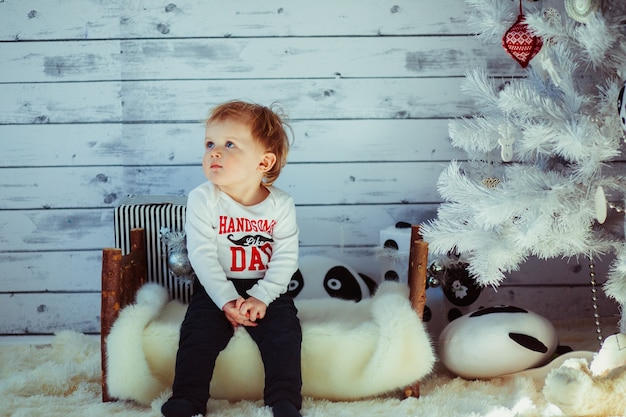 Little boy sits on toy bench under christmas tree