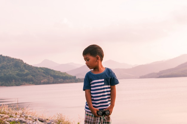 Little boy sitting alone at dam in the evening