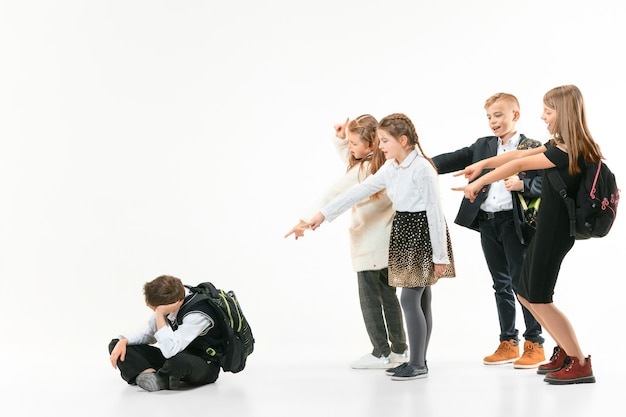 Little boy sitting alone on floor and suffering an act of bullying while children mocking