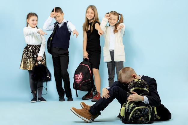 一人で床に座って、子供たちが嘲笑しながらいじめの行為に苦しんでいる小さな男の子