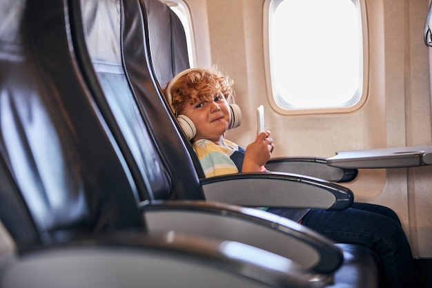 Little boy sitting alone with headphones and tablet on a plane