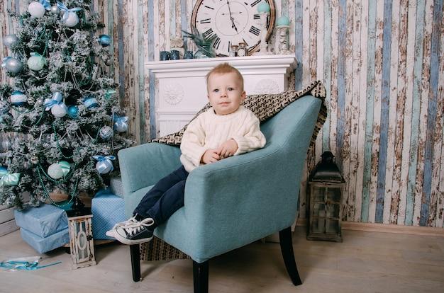 Little boy sitting in armchair near christmas tree
