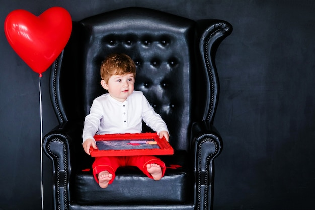 Little boy sitting on the armchair with red framed picture on the st. valentine's day.