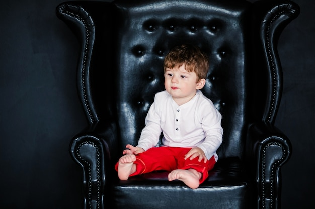 Little boy sitting on the armchair with red framed picture on the  valentines day