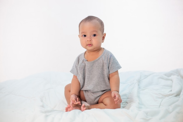 The little boy sitting on the bed