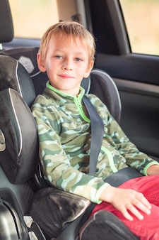 Little boy sitting on a car seat buckled up in the car.