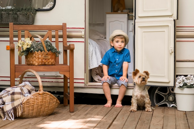 Little boy sitting on a caravan next to a cute dog