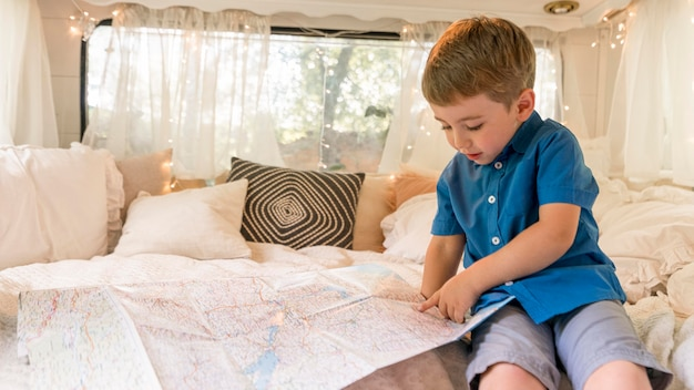 Little boy sitting in a caravan and looking on a map