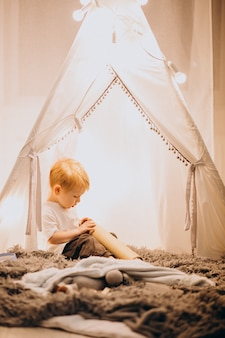 Little boy sitting in cozy tent with lights at home on christmas