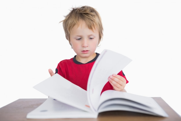 Little boy sitting at desk and reading book over white background