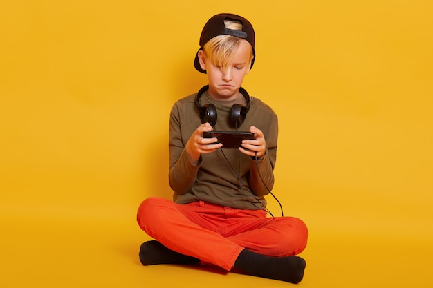 Little boy sitting on floor with smartphone in hands wearing trousers, cap and jumper, blond male child looks concentrated, playing his favourite online game. childhood concept.